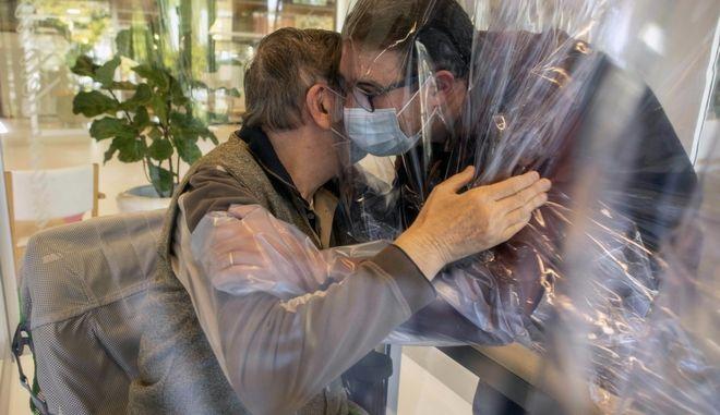 TΔύο άνδρες αγκαλιάζονται μέσα από πλαστικό παραπέτασμα για την αποφυγή του COVID-19 στο Castelfranco Veneto της Ιταλίας