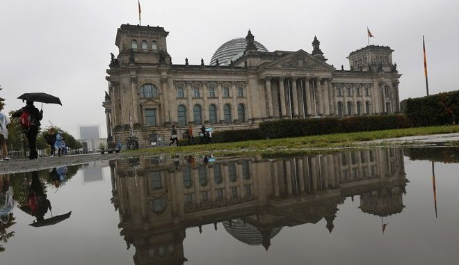 CORRECTS ORIENTATION OF THE IMAGE - The Reichstag building which hosts the German parliament is mirrored in a puddle in Berlin, Germany, Sunday, Sept. 24, 2017, when Germans election a new parliament. (AP Photo/Michael Probst)