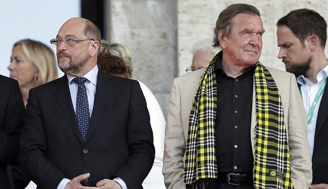 Martin Schulz, front left, chairman of the German Social Democratic Party (SPD) and Chancellor candidate for the upcoming general elections and former German Chancellor Gerhard Schroeder, front right, stay together prior to the German soccer cup final match between Borussia Dortmund and Eintracht Frankfurt in Berlin, Germany, Saturday, May 27, 2017. (AP Photo/Michael Sohn)