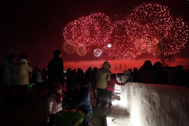 North Koreans watch as fireworks explode as part of New Year celebrations, above the Taedong River as viewed from Kim Il Sung Square, in Pyongyang, North Korea. (AP Photo/Jon Chol Jin)