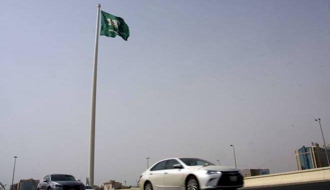 Vehicles pass under a giant Saudi flag in Jiddah, Saudi Arabia, Wednesday, June 21, 2017. Saudi Arabia's King Salman on Wednesday appointed his 31-year-old son Mohammed bin Salman as crown prince. (AP Photo/Amr Nabil)
