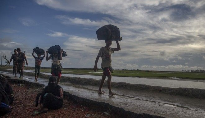 """Newly arrived Rohingya Muslims, who crossed over from Myanmar into Bangladesh, walk towards the nearest refugee camp at Teknaf, Bangladesh, Thursday, Sept. 28, 2017. More than 400,000 Rohingya Muslims have fled to Bangladesh since Aug. 25, when deadly attacks by a Rohingya insurgent group on police posts prompted Myanmar's military to launch """"clearance operations"""" in Rakhine state. (AP Photo/Dar Yasin)"""
