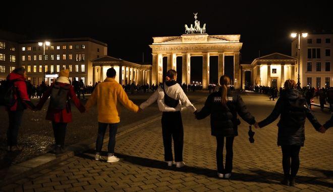 Άνθρωποι κρατούν τα χέρια καθώς σχηματίζουν μια ανθρώπινη αλυσίδα, κατά τη διάρκεια επαγρύπνησης για τα θύματα των πυροβολισμών στην κεντρική γερμανική πόλη Hanau