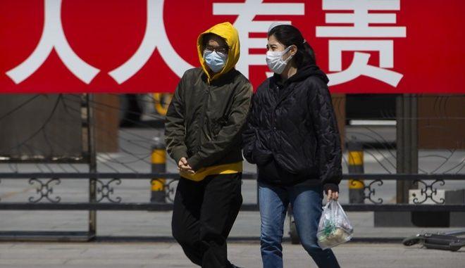 Πολίτες με μάσκα στην Κίνα (AP Photo/Mark Schiefelbein))