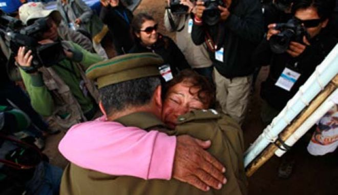 A relative of the 33 miners trapped deep underground in a copper and gold mine is hugged by a policeman after the T 130 drilling machine completed an escape hole for the 33 miners that are trapped deep underground at San Jose mine near Copaipo city October 9, 2010. REUTERS/Ivan Alvarado (CHILE - Tags: POLITICS ENERGY DISASTER BUSINESS IMAGES OF THE DAY)