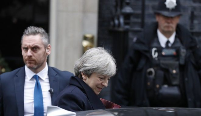 Police officers keep guard as Britain's Prime Minister Theresa May leaves 10 Downing Street to attend the weekly session of Prime Ministers Questions in Parliament in London, Wednesday, Dec. 6, 2017. (AP Photo/Kirsty Wigglesworth)