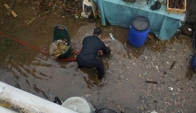 Πυροσβέστης επιχειρεί σε πλημμυρισμένο σπίτι στην Καλαμάτα