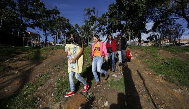 In this June 9, 2017 photo from left; Saraid Valbuena, carrying her 4-month-old daughter; Genesis Montilla; Heraly Obando; and Wilson Bernadette, all recently arrived to Colombia from Venezuela, walk towards a bus station in Bogota, Colombia. The group sells mangoes to make a living in hopes of sending a sliver of what they earn to relatives back home. But for many poor people fleeing Venezuelas triple-digit inflation, hours-long lines for food and medical shortages, Colombia is the journeys end. (AP Photo/Fernando Vergara)