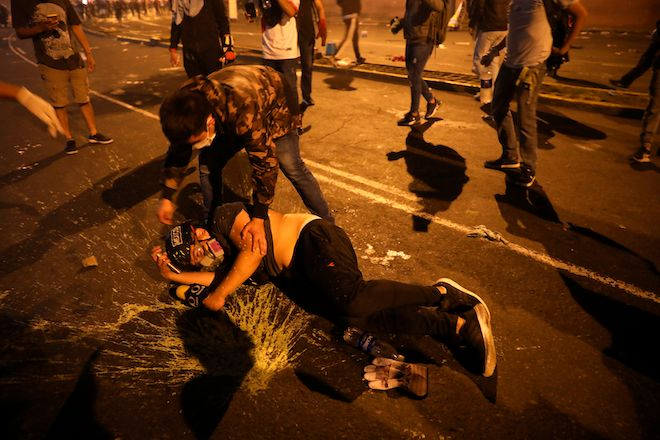 Ένας διαδηλωτής βοηθάει έναν δημοσιογράφο της Televisa που τραυματίστηκε κατά τη διάρκεια συγκρούσεων με την αστυνομία στην Plaza San Martin, 14 Νοεμβρίου 2020.