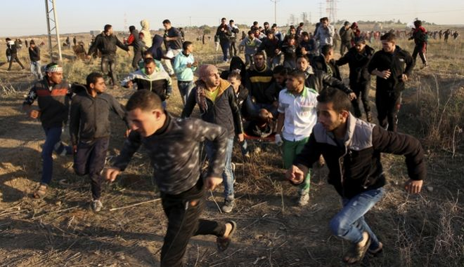 Palestinian protesters and medics evacuate a wounded youth during clashes on the Israeli border following a protest against U.S. President Donald Trump's decision to recognize Jerusalem as the capital of Israel, east of Gaza City, Friday, Dec. 8, 2017. (AP Photo/Adel Hana)