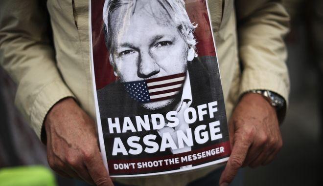 Διαδηλωτής κρατά αφίσα υπέρ της αθώωσης του Τζούλιαν Ασάνζ