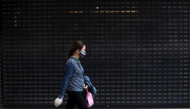 Μια γυναίκα φορά προστατευτκή μάσκα. Ο κορονοϊός στην Κύπρο.