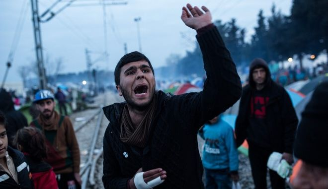 Refugees shout slogans during a protest asking for the opening of borders in a makeshift refugee camp near the village of Idomeni at the Greek - FYROM border on March 18, 2016.