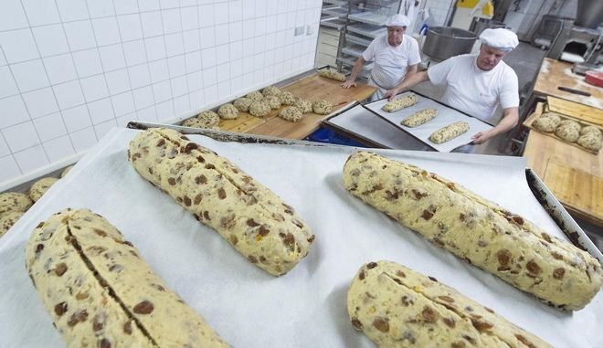 Employees  form and transport the dough of the Christmas fruit loafs Dresdner Christstollen (Dresden Stollen) in the Dresdner Backhaus GmbH bakery in Dresden, Germany, Friday, Nov. 14, 2014. The Stollen cake   contains dried fruit and is  covered with sugar, and it is usually eaten during the Christmas season. For more than 180 years the  bakery ships  Stollen around the world. Last year  it  exported the Stollen  to  more than 70 countries, more than 1,600 Stollen to the US. (AP Photo/Jens Meyer)