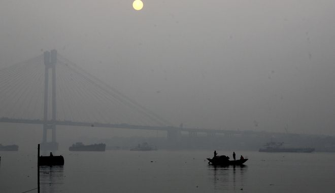 People on a country boat cross Hooghly River covered with fog as the sunsets in Kolkata, India, Saturday, Jan. 13, 2018. Fog engulfs many parts of the country during the winter months, disrupting normal life and throwing rail, air and road traffic out of gear. (AP Photo/Bikas Das)