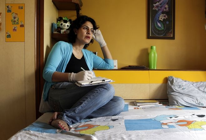 In this Friday, March 17, 2017 photo, Nidhi Chaphekar, Jet Airways flight attendant and a victim of the Brussels airport terror attack, pens down her thoughts at her residence in Mumbai, India. Chaphekar, 40, mother of two from Mumbai is one of the survivors of the last year's Brussels airport terror attack in which at least 30 people were killed and more than 200 wounded. Chaphekar said she has recovered 70 percent of her previous fitness level and would like to resume her passion, flying. (AP Photo/Rajanish Kakade)