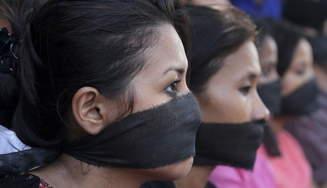 FILE - In this Aug. 24, 2013 file photo, photojournalists, with black bands around their mouth, participate in a protest against the gang rape of a female photojournalist in Mumbai, in Gauhati, India. The World Health Organization has declared violence against women an epidemic, calculating that one in three women worldwide will experience sexual or physical violence, most often from their husband or male partner. (AP Photo/Anupam Nath, File)