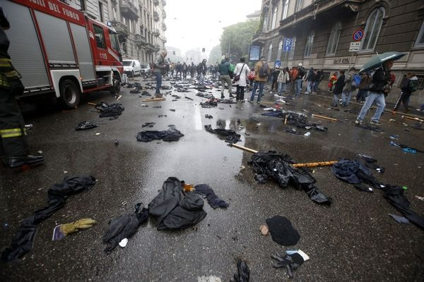 Clothes and objects lie on the ground after clashes broke out between demonstrators and police during a protest against the Expo 2015 fair in Milan, Italy, Friday, May 1, 2015. Dozens of people are protesting the opening of Milan's Expo 2015, torching parked cars, smashing bank and store windows and clashing with riot police far from the world's fair sprawling grounds. (AP Photo/Luca Bruno)