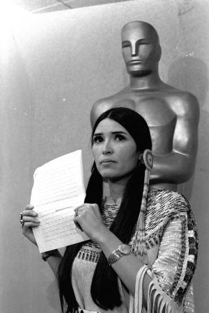 "A woman in Native American Indian dress, who indentified herself as Sacheen Littlefeather, tells the audience at the Academy Awards ceremony in Los Angeles March 27, 1973, that Marlon Brando was declining to accept his Oscar as best actor for his role in ""The Godfather.""  Littlefeather said Brando was protesting ""the treatment of the American Indian in motion pictures and on televison, and because of the recent events at Wounded Knee.""  (AP Photo)"