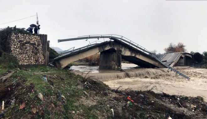 Local residents look at the collapsed bridge at the entrance of their village Mamuras, northern Albania, Friday, Dec. 1, 2017. At least one person has died during heavy rainfall that flooded many parts of Albania, paralyzing its ports and causing flights from its only international airport to be suspended, authorities said Friday. (AP Photo/Florent Bajrami)
