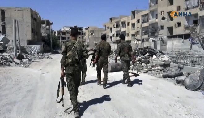 This frame grab from video released Thursday, Aug. 3, 2017 and provided by Hawar News Agency, a Syrian Kurdish activist-run media group, shows U.S.-backed Syrian Democratic Forces (SDF) fighters patrolling on a street in the northern city of Raqqa, Syria. U.S.-backed Syrian fighters clashed Thursday with members of the Islamic State group in Raqqa, the de facto capital of the extremists, opposition activists said. (Hawar News Agency via AP)