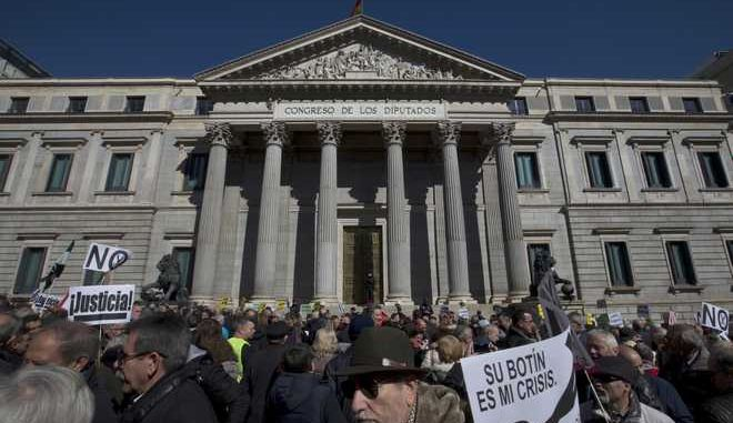 Thousands of pensioners block the area in front of the Spanish Parliament in Madrid, Spain, Thursday, Feb. 22, 2018. The pensioners are demanding decent pensions that keep up with inflation. Banners read ' Your booty, my crisis' and 'Justice'. (AP Photo/Paul White)
