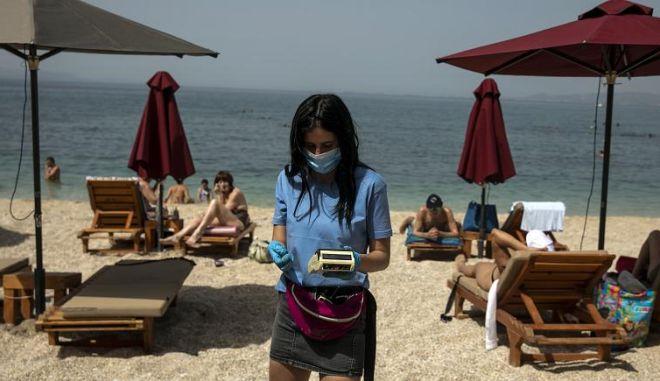Εργαζόμενη με μάσκα σε παραλία.