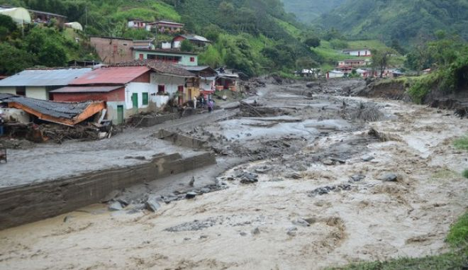 An overflooded ravine cuts through Salgar, in Colombia's northwestern state of Antioquia, Tuesday, May 19, 2015, where a deadly flood and mudslide swept through a day earlier. The avalanche of mud and debris roared through the mountain town before dawn Monday, taking away homes and bridges. Authorities said the death toll, which had risen to 62, was likely to grow throughout the day as an undetermined number of people remain missing. (AP Photo/Luis Benavides)