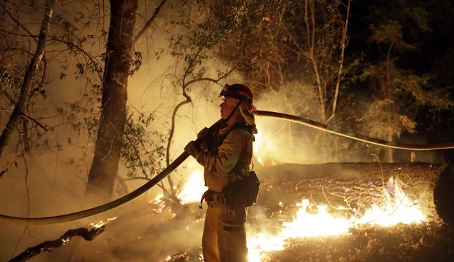 A firefighter holds a water hose while fighting a wildfire Saturday, Oct. 14, 2017, in Santa Rosa, Calif. (AP Photo/Marcio Jose Sanchez)
