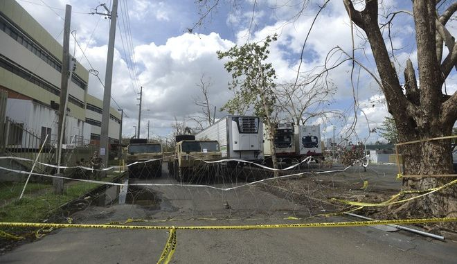 Three containers for holding corpses, right, are parked outside the Institute of Forensic Science, brought in to give support in the aftermath of Hurricane Maria in San Juan, Puerto Rico, Monday, Oct. 2, 2017. Juan Jose Diaz, a spokesman for the press at the institute, confirmed their facilities no longer provide enough space to store the bodies, and that several hospital morgues are also full. (AP Photo/Carlos Giusti)