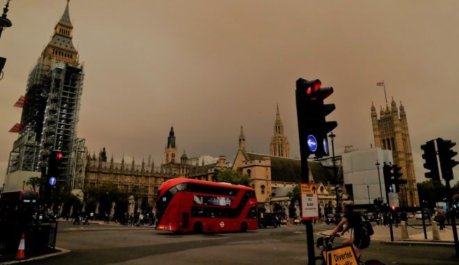 Big Ben and the Houses of Parliament are bathed in a dull  orange sky in London, Monday, Oct. 16, 2017. The unusual hue of the sky was thought to be due to the remnants of Hurricane Orphelia dragging in tropical air and dust from the Sahara. (AP Photo/Frank Augstein)