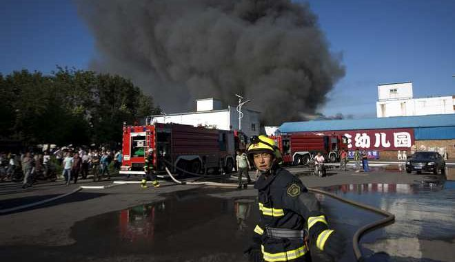 A firemen urges people to move away from a fire at a lumberyard in the south side of Beijing, China, Tuesday, June 30, 2015. The cause of the fire is under investigation and no casualties have been reported, according to Beijing Fire Department. (AP Photo/Andy Wong)