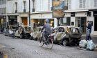 Ποδηλάτης δίπλα σε καμμένα αυτοκίνητα στο Παρίσι