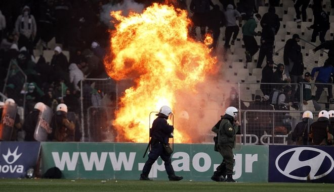 Riot police officers are attacked with fire bombs,thrown by Panathinaikos'   fans  during a soccer game for the Greek Super League at the Olympic stadium in Athens, Sunday, March 18 2012. The Greek league game between leader Olympiakos and Panathinaikos has been abandoned with eight minutes to go because of escalating clashes between fans and the police. (AP Photo/Kostas Tsironis)