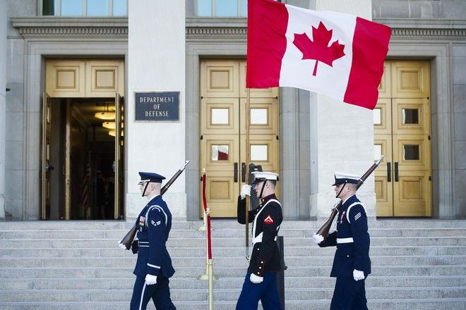 A military honor guard carries the Canadian flag past the Pentagon after the arrival of Canadian Defense Minister Harjit Sajjan for a meeting with Defense Secretary Jim Mattis, Monday, Feb. 6, 2017. (AP Photo/Cliff Owen)