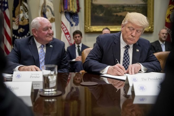 President Donald Trump, accompanied by Agriculture Secretary Sonny Perdue, signs an executive order during farmers' roundtable in the Roosevelt Room of the White House in Washington, Tuesday, April 25, 2017. (AP Photo/Andrew Harnik)
