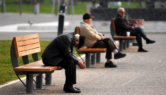 Ηλικιωμένοι κάθονται σε παγκάκι στην παραλία της Θεσσαλονίκης.