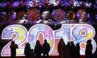 People stand in front of a 2018 sign in Octyabrskaya Square decorated to mark the upcoming Christmas and New Year celebrations in Minsk, Belarus, Friday, Dec. 22, 2017. (AP Photo/Sergei Grits)