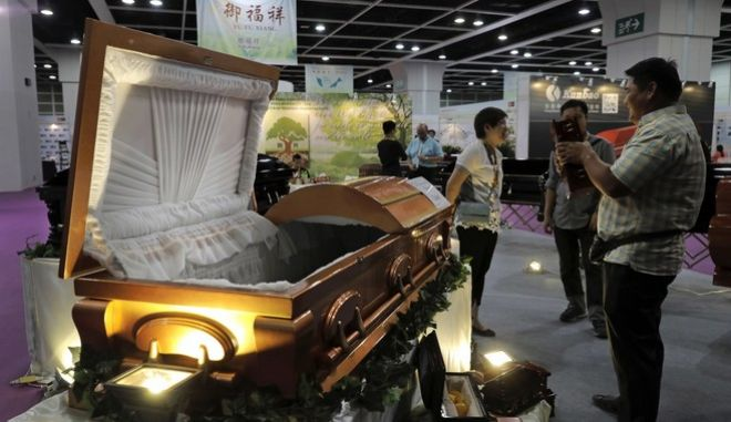 Visitors look at a paper casket at the Asia Funeral and Cemetery Expo & Conference in Hong Kong, Thursday, May 18, 2017. The expo underscores how for some investors, Asia's rapidly aging population makes its death industry a potentially lucrative market. Asia's aging population is projected to hit 923 million by mid-century, according to an Asian Development Bank, putting the region on track to become the oldest in the world. (AP Photo/Vincent Yu)