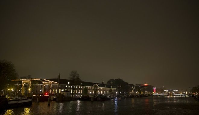 """Rain cloud covered skies and the reflection of the city lights prevented the Dutch from seeing the Supermoon in Amsterdam, Netherlands, Monday, Nov. 14, 2016. The brightest moon in almost 69 years was supposed to light up the skies over Amsterdam, during its closest approach to earth as the """"Supermoon"""" reached its most luminescent phase. (AP Photo/Peter Dejong)"""