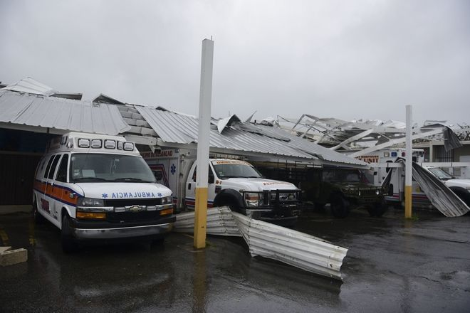 CORRECTS TO REMOVE REFERENCE OF HURRICANE CATEGORY - Rescue vehicles from the Emergency Management Agency stand trapped under an awning during the impact of Hurricane Maria, which hit the eastern region of the island, in Humacao, Puerto Rico, Wednesday, Sept. 20, 2017. The U.S. National Hurricane Center says Maria has lost its major hurricane status, after raking Puerto Rico. But forecasters say some strengthening is in the forecast and Maria could again become a major hurricane by Thursday. (AP Photo/Carlos Giusti)