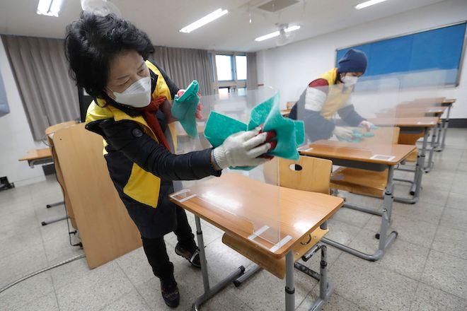 Ένας υπάλληλος απολυμαίνει το ημιδιαφανές πλαστικό διαχωριστικό που τοποθετείται ως προφύλαξη έναντι του κορονοϊού για τις εξετάσεις εισόδου στο πανεπιστήμιο, Σεούλ, Νότια Κορέα, 1 Δεκεμβρίου 2020.
