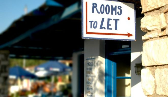 rooms to let sign in the greek islands with the background photographed intentionally fuzzy out of focus