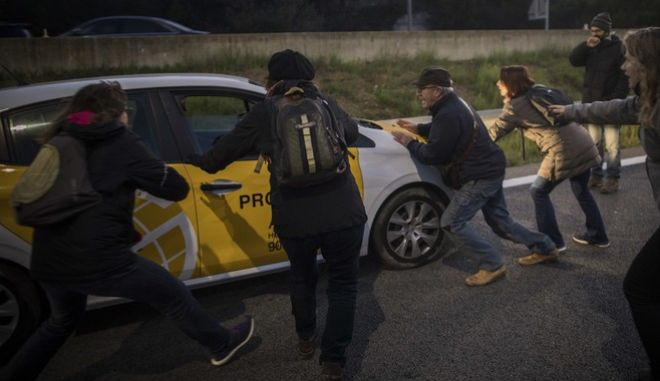 Demonstrators get ready to block a highway during the general strike in Barcelona, Spain, Wednesday, Nov. 8, 2017. A worker's union has called for a general strike Wednesday in Catalonia. The regional government was sacked by Madrid and many of its members jailed in a rebellion probe after pushing ahead with secession from Spain. (AP Photo/Santi Palacios)