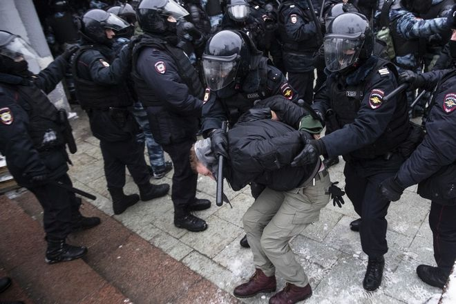Police officers detain a man during a protest against the jailing of opposition leader Alexei Navalny in Moscow, Russia, Saturday, Jan. 23, 2021. Russian police on Saturday arrested hundreds of protesters who took to the streets in temperatures as low as minus-50 C (minus-58 F) to demand the release of Alexei Navalny, the country's top opposition figure. (AP Photo/Pavel Golovkin)