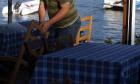 Σερβιτόρος ετοιμάζει τραπέζια. Φωτό αρχείου.