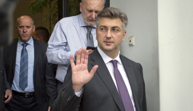 Croatia's Prime Minister, Andrej Plenkovic, waves as he leaves his party headquarters in Zagreb, Croatia, Thursday, April 27, 2017. Plenkovic has moved to replace three ministers from a junior party in the government, triggering a crisis in the ruling conservative coalition. (AP Photo/Darko Bandic)