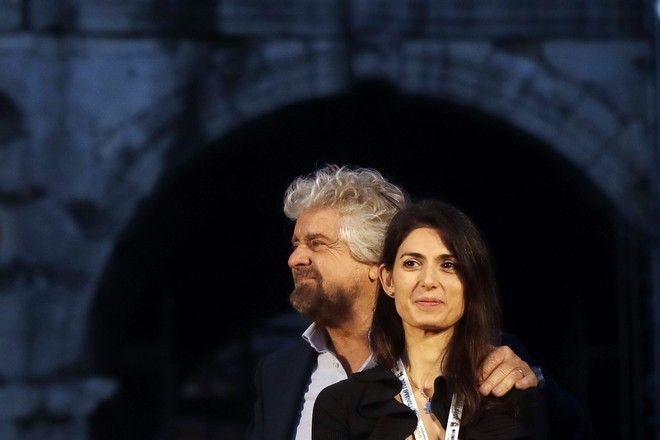 FILE - In this photo taken Saturday, Nov 26, 2016, Rome Mayor Virginia Raggi and 5-Star Movement leader Beppe Grillo attend a political rally in Rome. Rome's mayor is seeking to delay the start of her trial on charges that she lied about a City Hall appointment until after Italy's March 4 general election, where Raggi's anti-establishment 5-Star Movement is hoping to wrest control of the Italian government for the first time. (AP Photo/Gregorio Borgia)