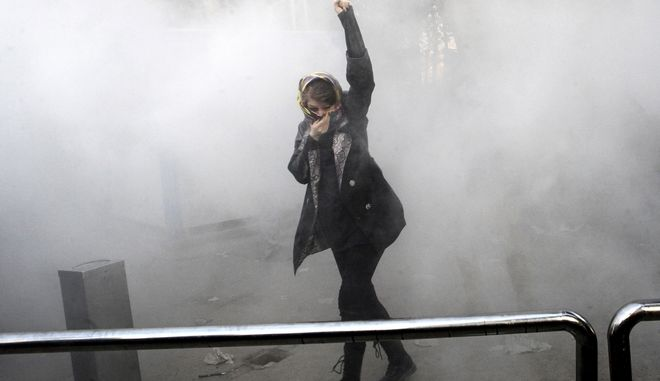 FILE - In this Dec. 30, 2017 photo made by an individual not employed by the Associated Press and obtained by the AP outside Iran, a university student attends a protest inside Tehran University while a smoke grenade is thrown by Iranian police, in Tehran, Iran. New unrest in Iran over the past 10 days appears to be waning, but anger over the economy persists. The protests in dozens of towns and cities also showed that a sector of the public was willing to openly call for the removal of Irans system of rule by clerics -- frustrated not just by the economy but also by concern over Irans foreign wars and general direction. (AP Photo, File)