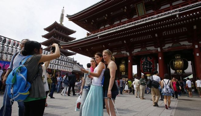 In this May 6, 2015 photo, foreign tourists take a picture at Sensoji Temple in Tokyo. The cheap yen, easier visas and other initiatives are luring foreign travelers eager to stretch their budgets and see some UNESCO World Heritage sites, bringing in welcome cash as well as myriad complications. (AP Photo/Shizuo Kambayashi)